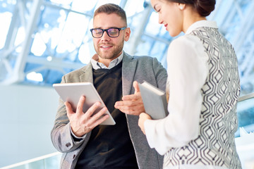 Low angle portrait of modern businessman holding digital tablet while talking to female colleague standing at glass balcony in office building