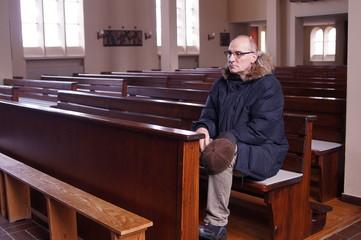 sad lonely senior man praying in a catholic church