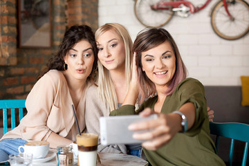 Female Friends In Cafe Taking Selfie Using Smart Phone. Drinking coffee, having fun and enjoying their time.