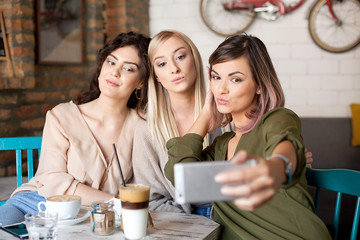 Female Friends In Cafe Taking Selfie Using Smart Phone. Drinking coffee, laughing and enjoying their time.