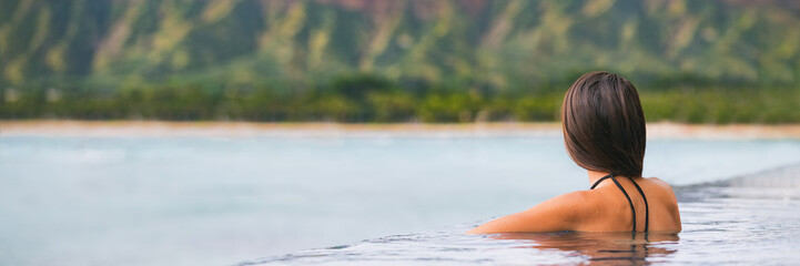 Luxury vacation woman travel tourist relaxing in infinity swimming pool on summer travel at...