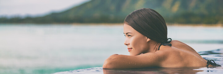Luxury vacation woman relaxing in infinity swimming pool on summer travel at beach resort. Asian girl tourist on wellness spa relaxation outside in nature landscape banner panorama.