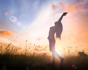 International migrants day concept: Silhouette of healthy woman raised hands for praise and worship God at autumn sunset meadow background.