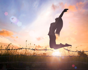 International human rights day concept: Silhouette of a girl jumping over broken barbed wire at autumn sunset meadow with her hands raised