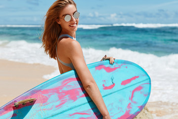 Happiness, healthy lifestyle and recreation concept. Beautiful smiling female model in trendy shades, carries kite board, waits waves on ocean, has positive expression, poses at beach near ocean