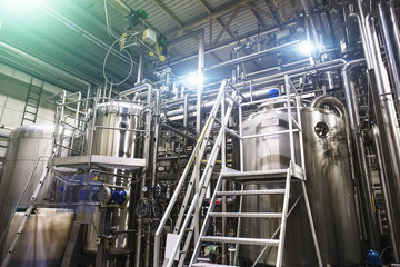 Stainless steel brewing equipment : large reservoirs or tanks and pipes in modern beer factory. Brewery production, industrial background
