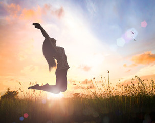International human rights day concept: Silhouette of happy woman jumping with her hands raised at autumn sunset background.