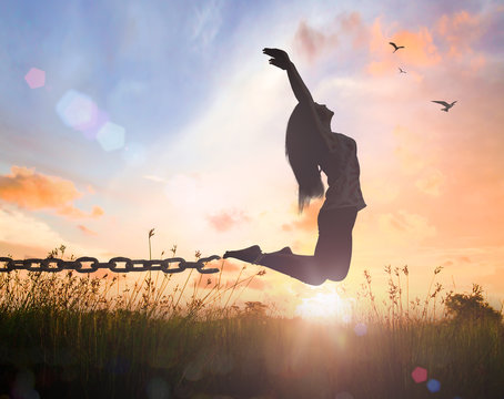 Individual human right day concept: Silhouette of a woman jumping and broken chains at orange meadow autumn sunset  with her hands raised