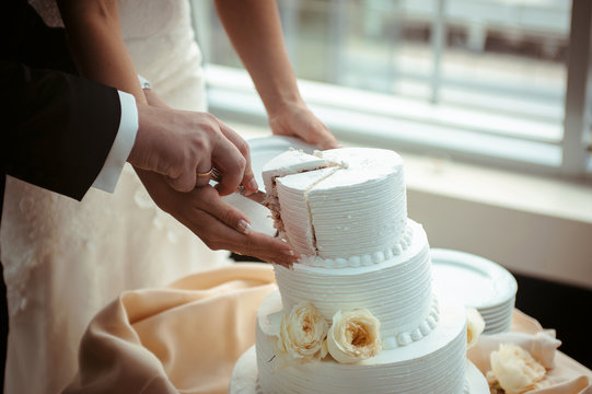 A bride and a groom is cutting their wedding cake. beautiful cake. nicel light. wedding concept