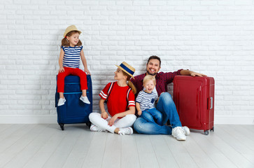 concept travel and tourism. happy family with suitcases near   wall