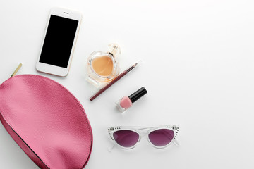 Bottle of perfume, smartphone and cosmetic products on white background