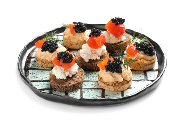 Plate of delicious canapes with black caviar on white background