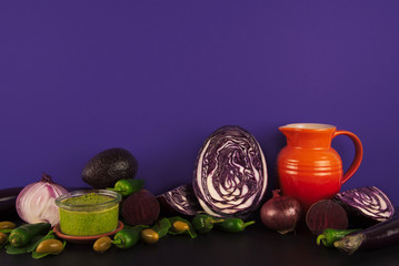 Assortment of raw organic purple and green vegetables.