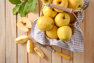 Basket with ripe yellow apples on wooden background