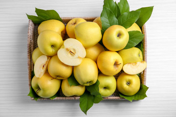 Wicker tray with ripe yellow apples on light background