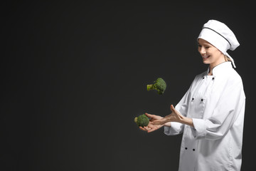Female chef in uniform with broccoli on black background
