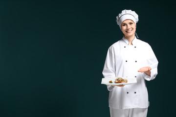 Female chef in uniform with tasty dish on dark background
