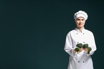 Female chef in uniform with broccoli on dark background