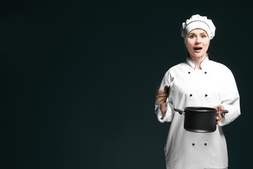 Female chef in uniform with saucepan on dark background
