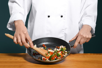 Female chef in uniform cooking tasty dish on table, closeup