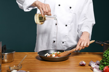 Female chef in uniform adding oil to tasty dish on table, closeup