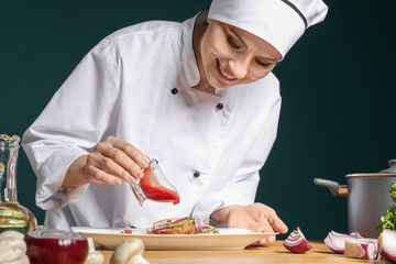 Female chef in uniform adding sauce to tasty dish on table