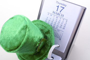 St Patrick's Day calendar for March 17 with green leprechaun hat on white wood table.