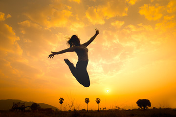 Silhouette of happy woman jumping over sunrise. Concept image for symbolic of successful, image made warmth tone.