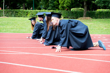 Graduation group of students celebrating on athletic track, preparing to race. Students competiting in a race on athletic track after graduating.