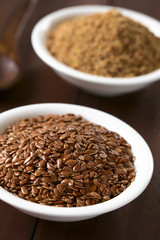 Whole brown flax seeds or linseeds and ground linseeds in small bowl, photographed on dark wood with natural light (Selective Focus, Focus one third into the image)