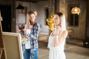 Beautiful young woman painting her model