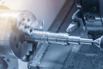 The CNC lathe machine cutting the brass shaft  by lathe tool.