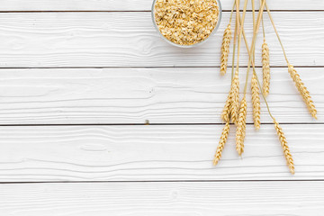 Cereals background. Raw oatmeal near sprigs of wheat on white wooden background top view copy space
