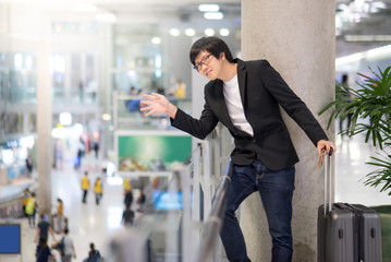 Young asian man with suitcase luggage raising hand for greeting with his friend in the international airport terminal, business travel concept
