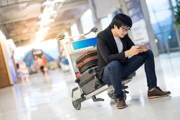 Young Asian man using smartphone sitting on airport trolley with his suitcase luggage in the international airport terminal, business travel concepts