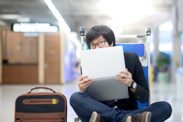 Young asian man posing with laptop computer on airport trolley during waiting for a connecting flight, freelance lifestyle and digital nomad concepts