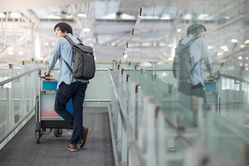 Young Asian man walking with airport trolley and his suitcase luggage in the international airport terminal, arrival from travel abroad