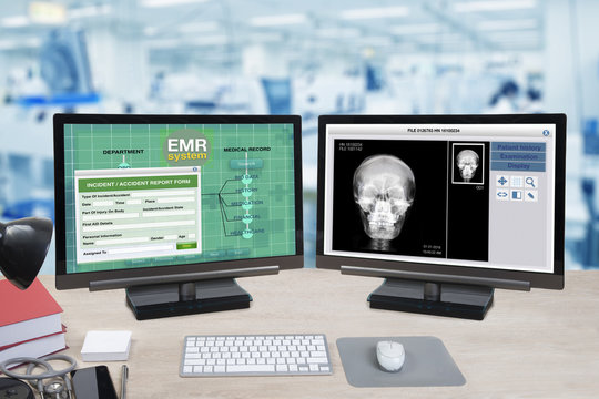 Health information and patient x-ray show on two computer monitors on doctor desk.