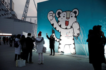 A woman poses for photographs with Soohorang, the mascot for the Pyeongchang 2018 Winter Olympics at the Medal Plaza in Pyeongchang