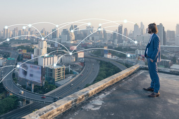 Wall Mural - young business man standing on a roof and looking at city with network connection technology