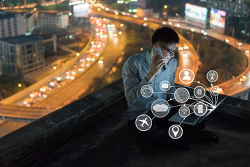 Wall Mural - young business man sitting talking mobile phone and working at night on rooftop, and icon technology concept