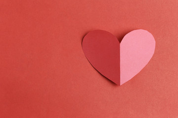 Heart shape of paper on the red cardboard background.