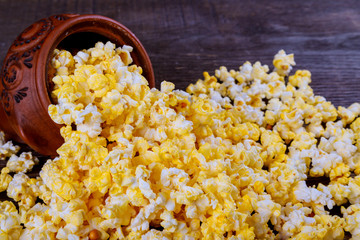 Salt popcorn on the wooden background . With space for text