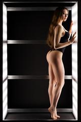 Fashion photo of young beautiful woman in black  underwear in light in dark studio