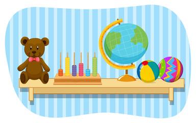 Teddy bear and globe on wooden shelf
