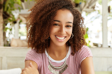 Close up shot of dark skinned female with frizzy hair, broad smile, recreats alone in cafe, being in good mood. Photo of positive African woman enjoys rest during weekend at cozy restaurant.