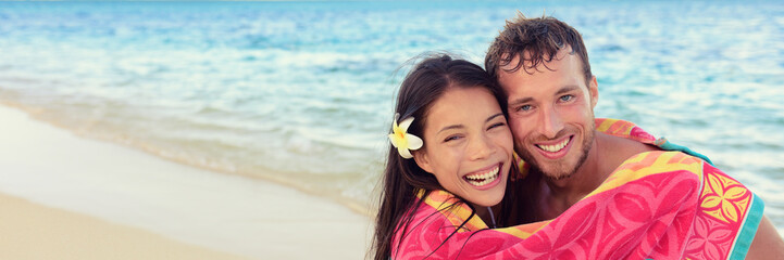 Happy couple summer fun hugging under towel on beach vacation. Laughing young people cuddling in Hawaii holiday banner panorama. Asian girl, Caucasian man interracial friends.
