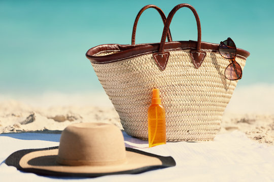 Sun care vacation accessories to bring in your beach bag for Caribbean holidays - sunglasses, sun hat, sunscreen solar lotion for sun protection.