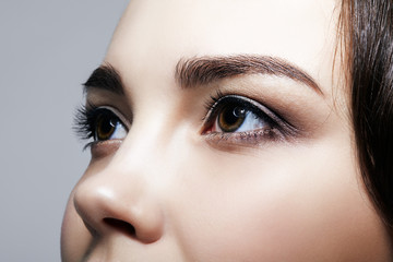 Closeup macro shot of  human  female face on gray background. Woman with natural nude face beauty makeup