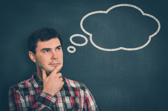 Thoughtful man with thought bubble on blackboard